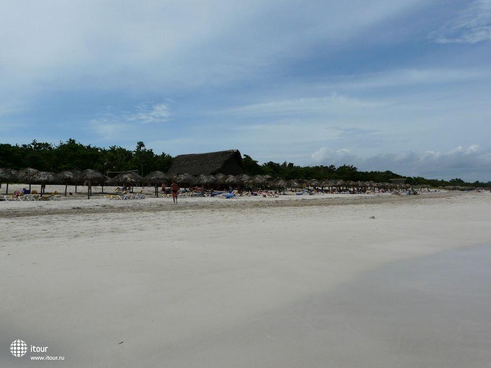 Часть пляжа с пляжным баром посередине.